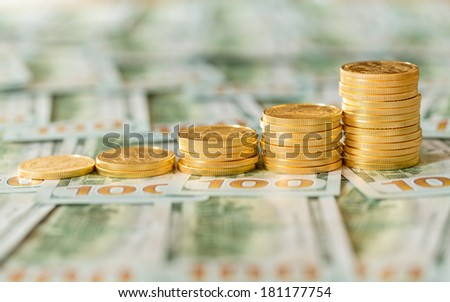 Stack of golden eagle coins in rising price graph or bar chart and standing on new design of US currency one hundred dollar bills - stock photo