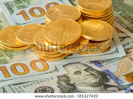 Stack of golden eagle coins on new design of US currency one hundred dollar bills with Benjamin Franklin portrait - stock photo