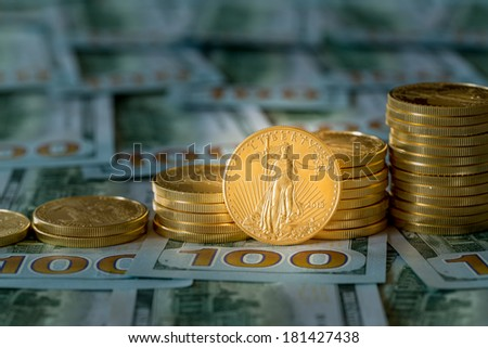 Stack of golden eagle coins on new design of US currency one hundred dollar bills with spotlight on the Liberty statue on one coin - stock photo