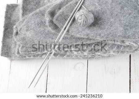 Stack of gray warm fluffy socks with knit needles and ball on white wood. - stock photo