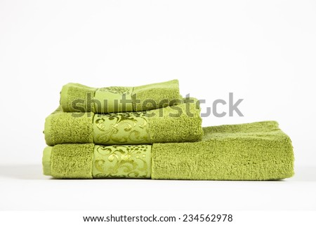 stack of green bathroom towels on white background - stock photo
