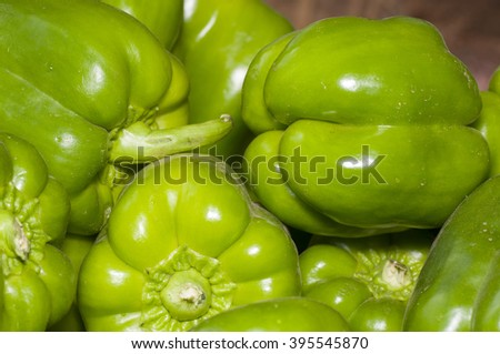Stack of green capsicum (bell pepper) in market. - stock photo