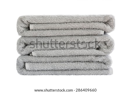 Stack of grey bath towels. Isolated over white - stock photo