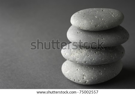 Stack of grey massage stones on dark grey background. - stock photo