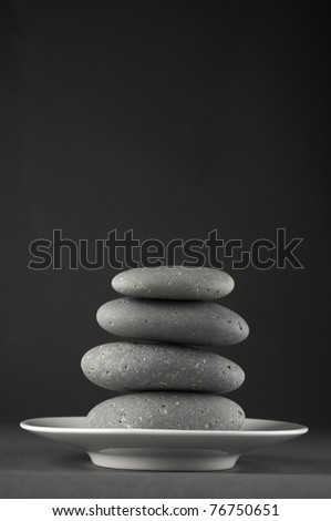Stack of grey massage stones on white plate against dark grey background. - stock photo