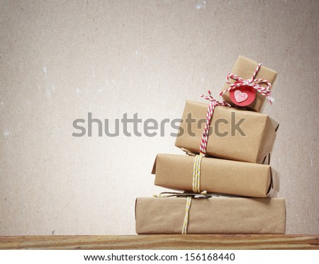 Stack of handcraft gift boxes on wooden board with a natural textured background - stock photo