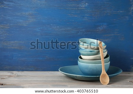 Stack of handmade blue ceramic bowls and wood spoon on rustic wooden table against blue painted wooden wall. - stock photo