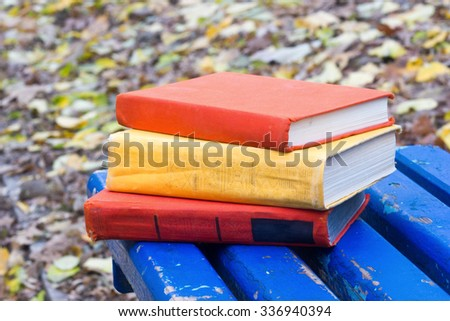 Stack of hardback book and lying on a bench at park on blurred nature backdrop. Copy space, back to school. Education background. - stock photo