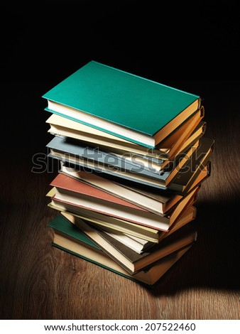 Stack of hardcover books arranged haphazardly viewed from a high angle on a wooden desk or table with copyspace and shadow behind