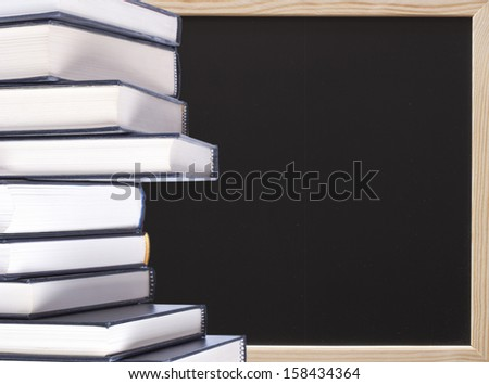 Stack of hardcover books with chalkboard background