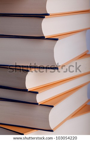 Stack of hardcover books with spines facing away from the camera on a white background