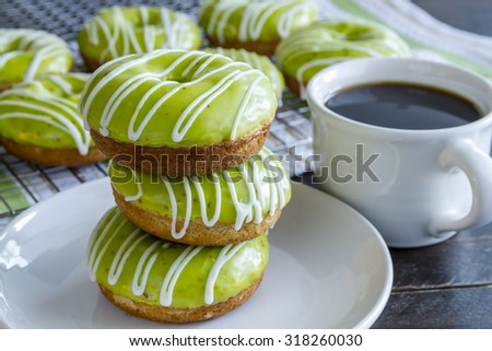 Stack of homemade baked caramel apple donuts with green apple glaze sitting on white plate with cup of coffee - stock photo