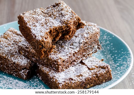Stack of homemade double chocolate chunk brownies dusted with powdered sugar sitting on bright blue plate - stock photo