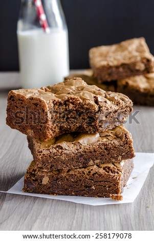 Stack of homemade double chocolate chunk brownies sitting on table with glass of milk with red straw - stock photo