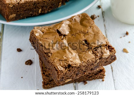 Stack of homemade double chocolate chunk brownies sitting on white wooden table