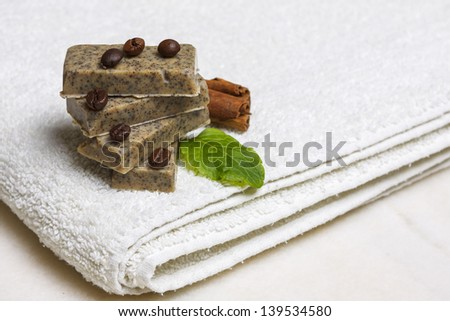 Stack of homemade flavored soap bars surrounded by coffee beans, cinnamon and lavender leaf on white towel. - stock photo