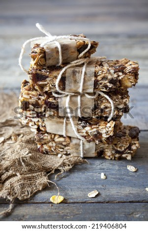 stack of homemade granola bars with dried fruits and handmade packaged on vintage blue wooden background - stock photo