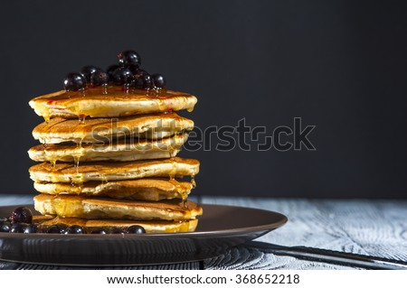 Stack of homemade pancakes with berries and honey on brown plate on rustic background. Russian holiday pancake week. Focus on pancakes. Horizontal view. - stock photo