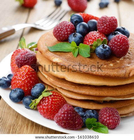 Stack of homemade pancakes with strawberries raspberries and blueberries on white plate - stock photo