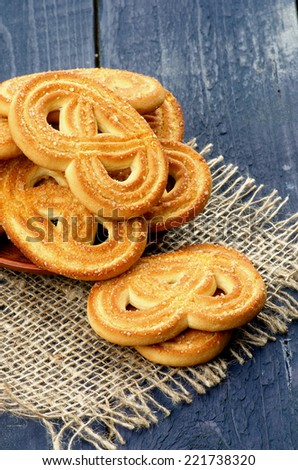 Stack of Homemade Shape Pretzel Sugar Cookies closeup on Sackcloth isolated on Dark Blue Wooden background
