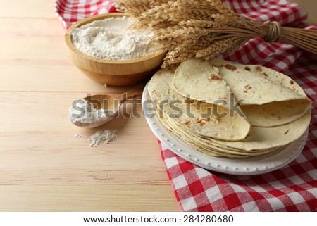 Stack of homemade tortilla on plate, on wooden table background - stock photo