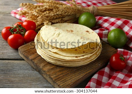 Stack of homemade whole wheat flour tortilla and vegetables on cutting board, on wooden table background - stock photo