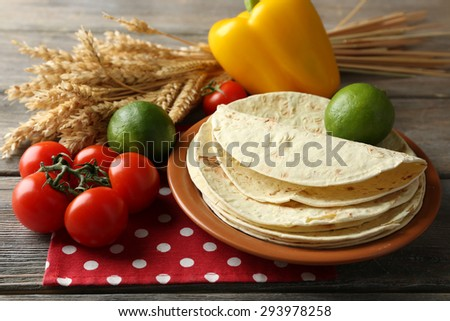 Stack of homemade whole wheat flour tortilla and vegetables on plate, on wooden table background - stock photo