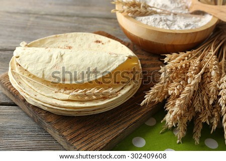 Stack of homemade whole wheat flour tortilla on cutting board, on wooden table background - stock photo
