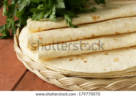 stack of homemade whole wheat flour tortillas on a wooden table - stock photo