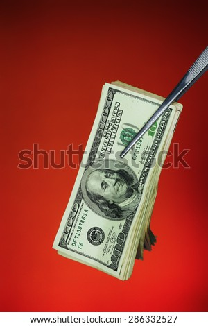 Stack of hundred-dollar bills being held with forceps against a grungy red background.
