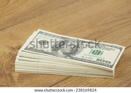 Stack of hundred-dollar bills on wooden background - stock photo