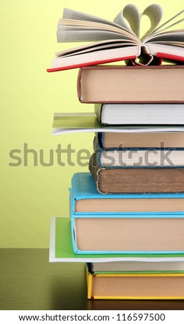 Stack of interesting books and magazines on wooden table on green background - stock photo