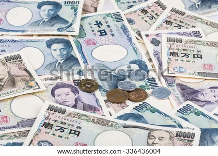 Stack of Japanese currency yen or Japanese banknotes and Japanese yen coins  - stock photo