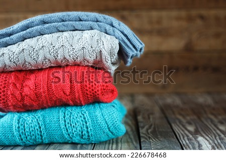 Stack of knitted sweaters on wooden background. - stock photo