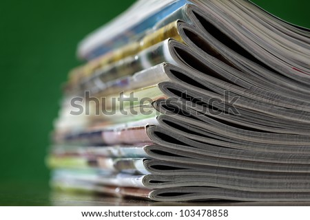 Stack of magazines against green background - stock photo