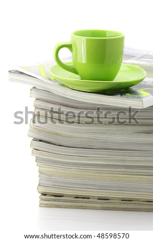 Stack of magazines and green cup of coffee isolated on white background.