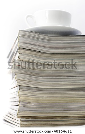Stack of magazines and white cup of coffee on light background.