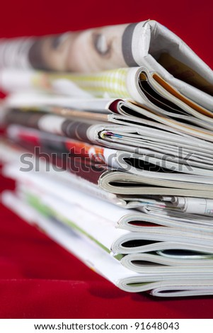 stack of magazines isolated on red - stock photo