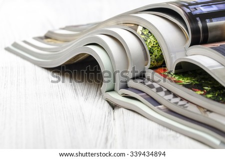 stack of magazines on a white-painted wooden table - stock photo