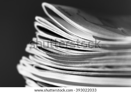 Stack of magazines on black background with swallow depth of field, black and white photo