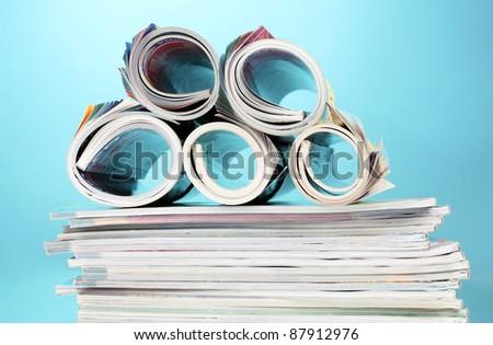 stack of magazines on blue background - stock photo