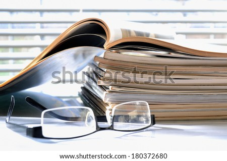 Stack of magazines with black glasses - stock photo