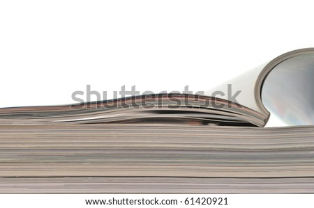 Stack of magazines with opened one on white background