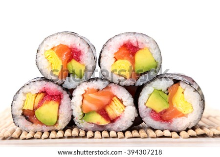 Stack of maki sushi on bamboo mat with white background