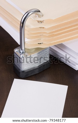 Stack of manila folders closed with a metal lock. Add your text to the white space. - stock photo