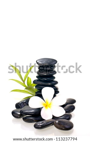 Stack of many black zen stone with white plumeria flower - stock photo