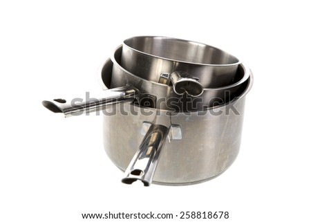 Stack of metal saucepans on a white background - stock photo
