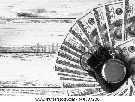 Stack of money dollars laid out like a fan with antique gold watch on white retro stylized wood background black and white - stock photo