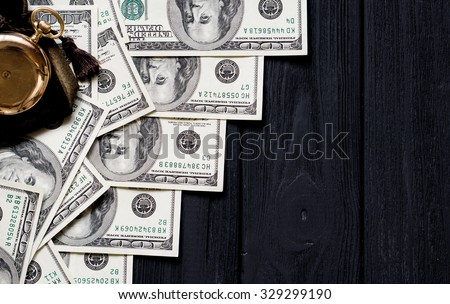 Stack of money dollars laid out like a ladder with antique gold watch on black retro stylized wood background - stock photo