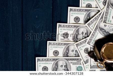 Stack of money dollars laid out like a ladder with antique gold watch on dark blue retro stylized wood background - stock photo